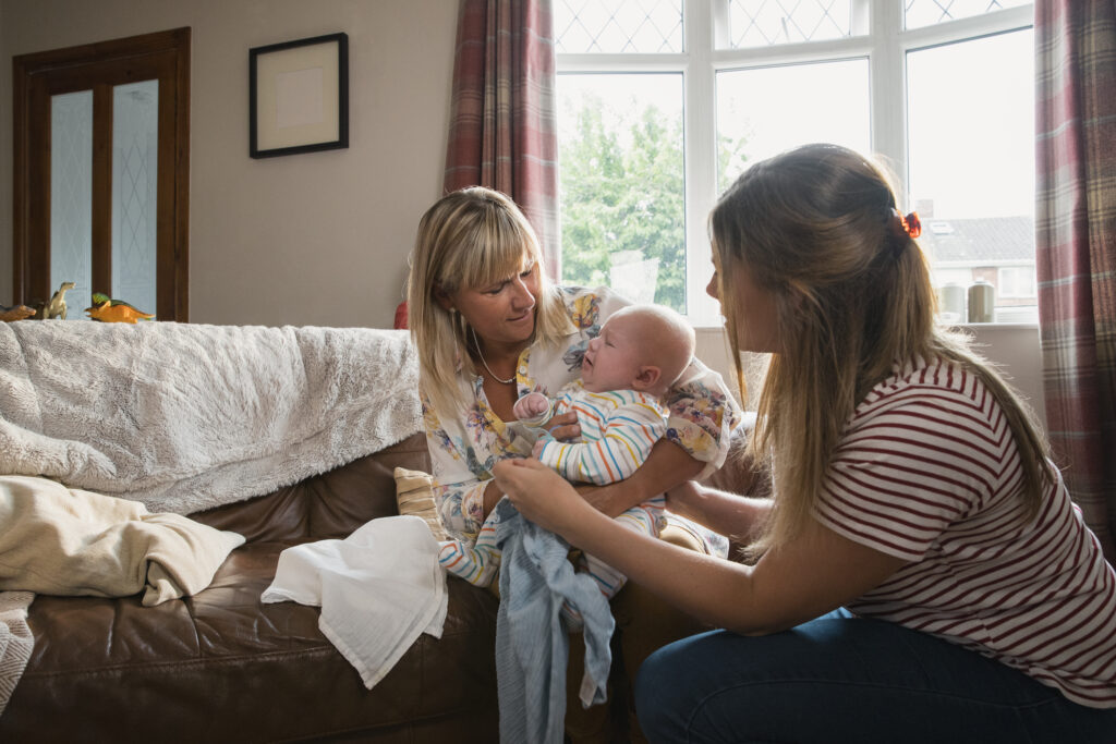 Home visitor holding newborn baby as mom leans in