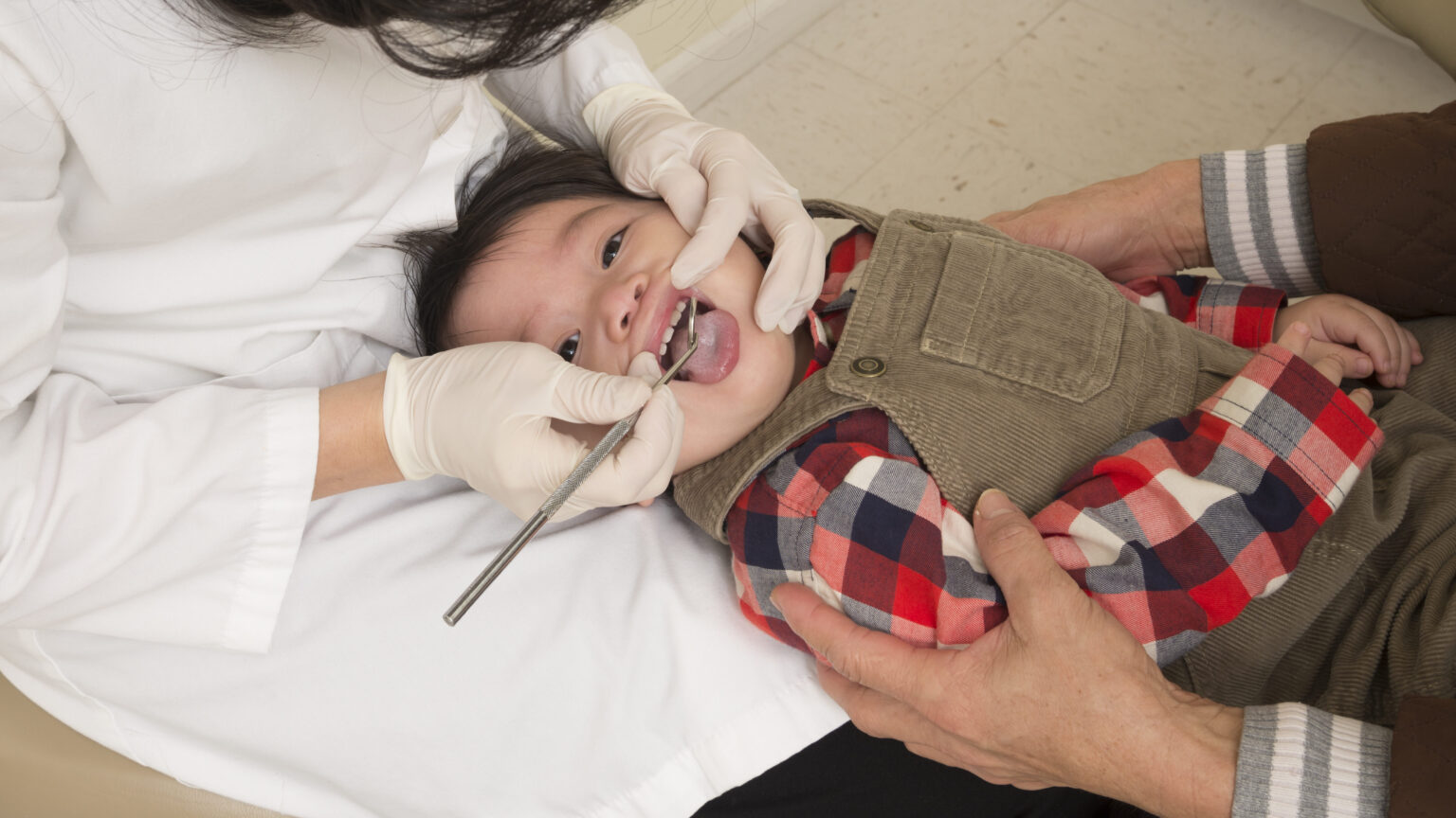 a photograph of a parent holding his todler for a dentist