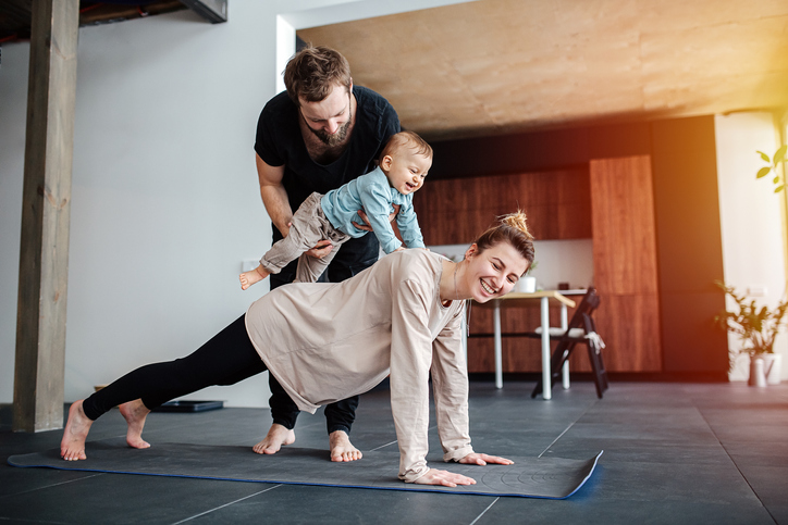 Mother doing plank, father holding their baby on her back,
