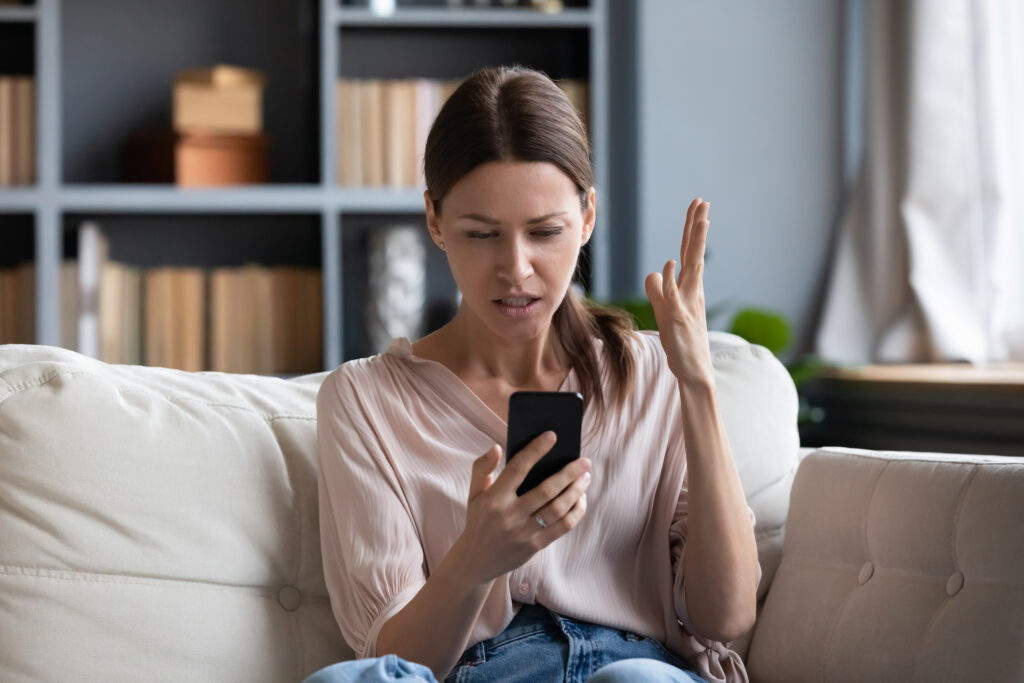 Unhappy young female looking at phone screen