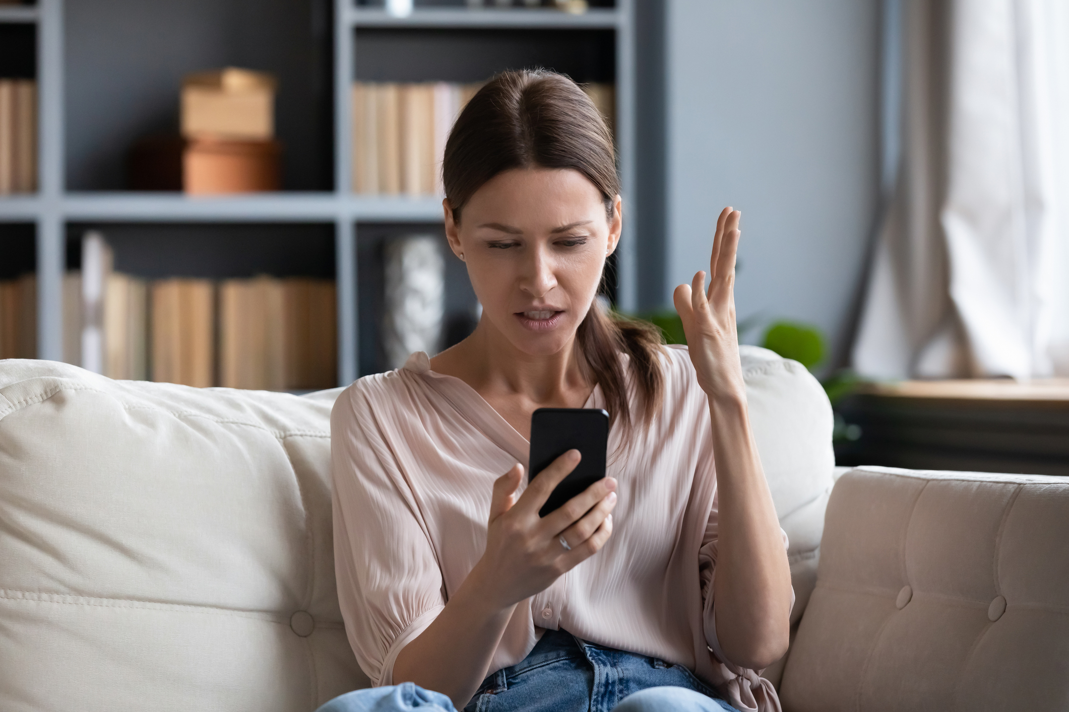 Woman looking at phone and confused