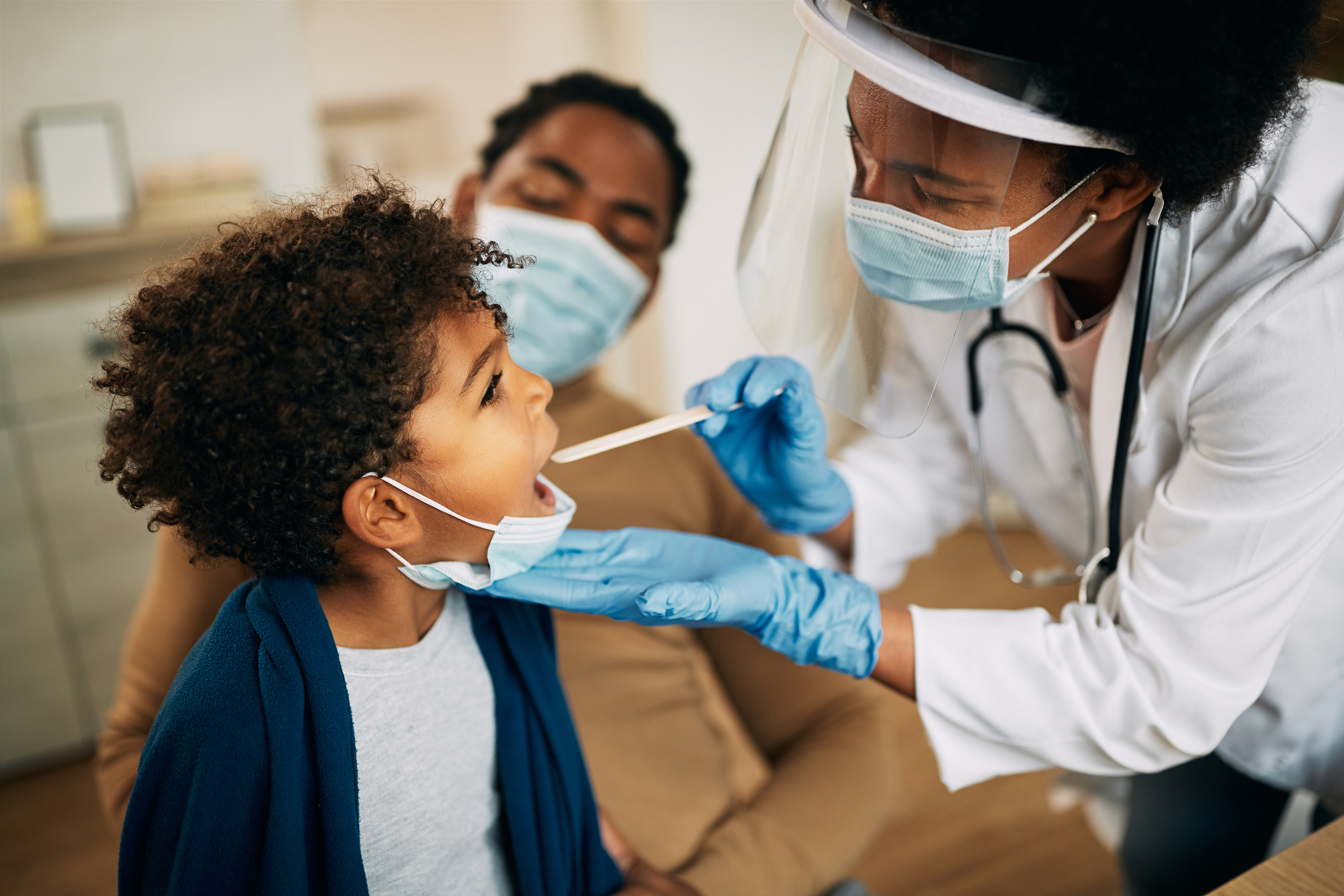 doctor with face mask examining boy's throat during a home visit.